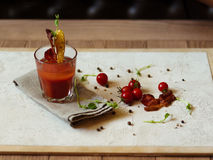 Tomatoes, peppercorns and green leaves on a table. An alcohol co Royalty Free Stock Photography