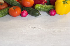 Tomatoes, peppers, cucumbers and radishes are on the table.  Stock Photo