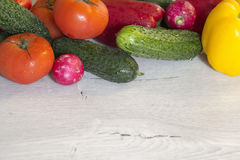 Tomatoes, peppers, cucumbers and radishes are on the table.  Royalty Free Stock Photography