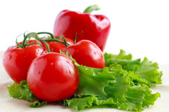 Tomatoes, peppers and lettuce on a napkin. Isolated on white Stock Image