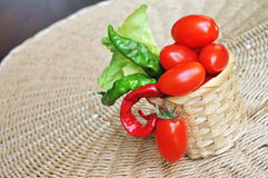 Tomatoes, peppers and salad in wicker basket. There are some tomatoes, peppers and salad in wicker basket Royalty Free Stock Photo