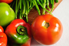 Tomatoes, peppers and scallions. Fresh salad ingredients on dinner table Royalty Free Stock Images