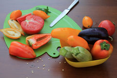 Tomatoes and peppers sliced on cutting board оn table. Close up. Tomatoes and peppers sliced on cutting board оn wooden table. Nearby there is dish with Royalty Free Stock Photos