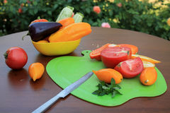 Tomatoes and peppers sliced on cutting board оn table in flower. Tomatoes and peppers sliced on cutting board оn wooden table in flowers background. Nearby Royalty Free Stock Images
