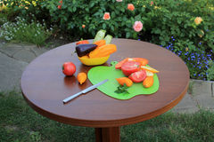 Tomatoes and peppers sliced on cutting board оn table in garden. Tomatoes and peppers sliced on cutting board оn wooden table in garden patio with flowers Royalty Free Stock Photography