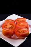 Tomatoes on plate. Tomato halves on white plate, black background stock images