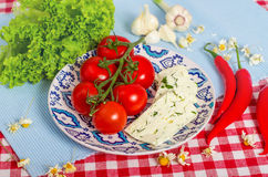 Tomatoes on the plate with cheese. Tomatoes on the pattern plate with cheese and lettuce Royalty Free Stock Image