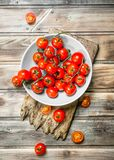 Tomatoes on a plate on a cutting Board. On wooden background stock photo