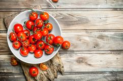 Tomatoes on a plate on a cutting Board. On wooden background stock photography