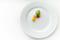 Tomatoes on a plate. Tomatoes on a white plate Royalty Free Stock Photo