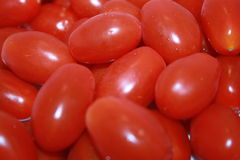 Tomatoes. Plum tomatoes piled together to produce a close up of this fruit Royalty Free Stock Images