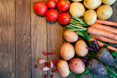 Tomatoes, potatoes, carrots, red beets on a wooden table. Vegetables. Tomatoes, potatoes, carrots, red beets on a wooden table Royalty Free Stock Photo