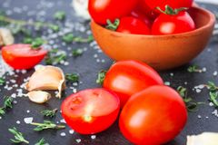 Tomatoes in a dish on a black background. Tomatoes in preparation. Tomatoes for the sentencing of lettuce and other dishes. Cook prepares dishes from tomatoes stock images