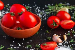 Tomatoes in a dish on a black background royalty free stock image