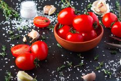 Tomatoes in a dish on a black background stock photos