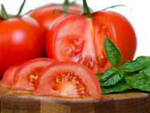 Tomatoes presentation sliced on wooden plank macro Stock Image