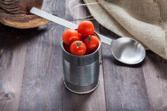 Tomatoes in a preserve tin. On a back table Stock Photos