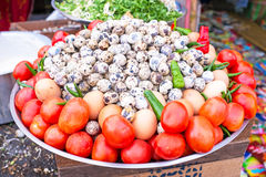 Tomatoes and quail eggs on a scale Royalty Free Stock Photos