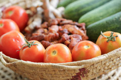 Tomatoes. Red tomatoes with cucumber and galangal, tamarind fruit basket Royalty Free Stock Photos