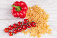 Tomatoes, red pepper and macaroni on table. Tomatoes, red pepper and macaroni on white table Stock Images