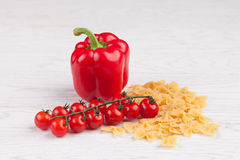 Tomatoes, red pepper and macaroni on table. Tomatoes, red pepper and macaroni on white table Royalty Free Stock Images