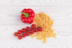 Tomatoes, red pepper and macaroni on table. Tomatoes, red pepper and macaroni on white table Stock Photo