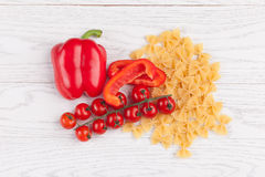 Tomatoes, red pepper and macaroni on table. Tomatoes, red pepper and macaroni on white table Royalty Free Stock Image