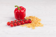 Tomatoes, red pepper and macaroni on table. Tomatoes, red pepper and macaroni on white table Royalty Free Stock Photo