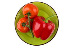 Tomatoes and red sweet pepper in green plate on white Stock Photos