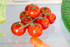 Tomatoes in the refrigerator with the door open.  Royalty Free Stock Photo