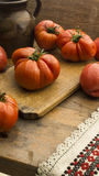 Tomatoes on rustic wooden chopping board and wooden table. Tomatoes 029 on rustic wooden chopping board and wooden table. High resolution image Royalty Free Stock Photo