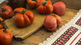 Tomatoes on rustic wooden chopping board and wooden table Royalty Free Stock Photo