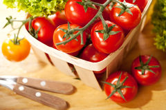 Tomatoes and salad in basket on wooden table. Tomatoes and salad in wooden basket on table Stock Photo