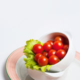 tomatoes with salad leaves in a bow Stock Photography