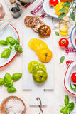Tomatoes salad making. Green,yellow and red ripe tomatoes on  white marble cutting board and white wooden background with ingredie Royalty Free Stock Photo