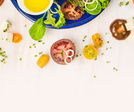 Tomatoes salad making with oil and cress on white wooden background Royalty Free Stock Images