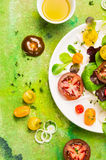 Tomatoes salad with olive oil on green background, top view Royalty Free Stock Photo