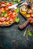 Tomatoes salad with various colorful tomatoes, olives oil and Balsamic vinegar . Plate with tomatoes salad, cutlery and ingredien stock image