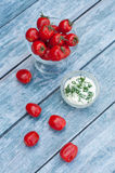 Tomatoes and sauce. Red cherry tomatoes in a small bowl and sauce. Fresh organic tomatoes. Blue background, which is stylized as the old board Stock Photos