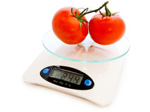 Tomatoes at scale Royalty Free Stock Photos