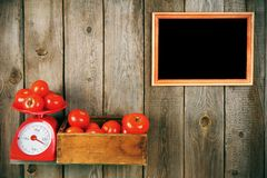 Tomatoes on scales and in a box Royalty Free Stock Image