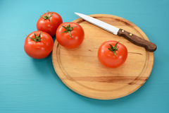 Tomatoes with a serrated knife on a wooden board Stock Photography