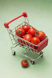 Tomatoes in shopping trolley, on green backdrop Stock Photo
