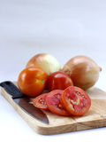 Tomatoes sliced and onions on wood cutting board. Fresh tomatoes sliced and onions with knife on wood cutting board stock photo
