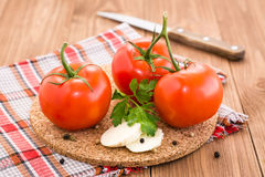 Tomatoes, slices of cheese and parsley on a substrate on a wooden table Stock Photography