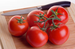 Tomatoes on slicing board Royalty Free Stock Images