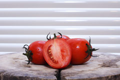 Tomatoes. Slicing tomatoes on a wooden chopping board Royalty Free Stock Photo