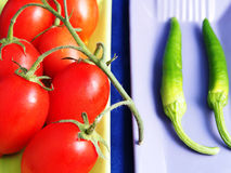 Tomatoes and small green peppers Stock Images