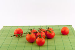 Tomatoes. Small tomatoes with water droplets on white background stock image
