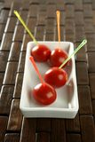 Tomatoes snack and colored sticks Stock Photos